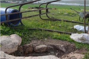 アル・ハディディーヤ村の歴史的な井戸。背後にロイ入植地がある。